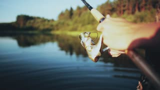 Close-up view of male hands holding the fishing rod. Young Fisher man twisting the rod with spinning reel.