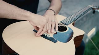 Close-up view of male hands holding the guitar and making repair. Musician man changing the string on instrument.