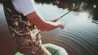 Close-up view of male hands uses the rod with spinning reel. Fisher man spending time in the nature alone.