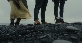 Close-up view of people foot standing on the black volcanic beach in Iceland. Tourist exploring the island.