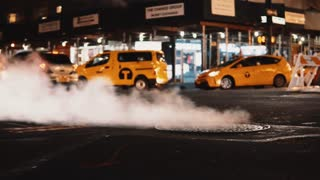 Close-up view of smoke coming from manhole cover on the traffic road in downtown of New York, America.