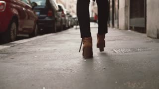 Close-up view of stylish woman walking in little street. Girl wearing shoes on heels goes through the city. Slow motion.