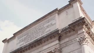 Close-up view of the Arch of Titus in Rome, Italy. Camera moving down.