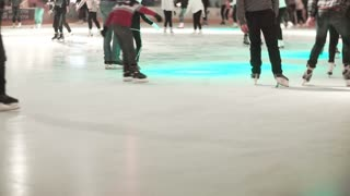 Close-up view of the crowd skating in the ice with colored light on a skating rink together.