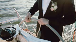 Close-up view of the groom in a wedding suit standing behind steering wheel on the yacht. Man driving the ship in sea.