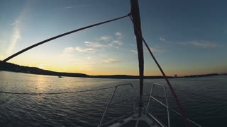 Close-up view of the nose part of sailboat. Beautiful water landscape on sunset. Yacht splashing the waves.