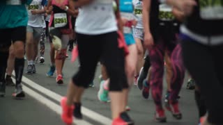 Close-up view of the people s feet in sportswear and sneakers running the marathon of a long distance at city festival.