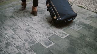 Close-up view of the young woman with suitcase walking through the street, arrives to the new city and going to hotel.