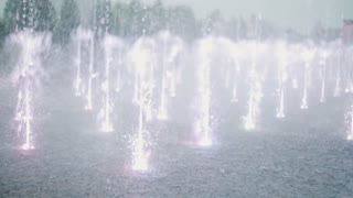 Close-up view of water and light show at the fountain. Children running through the jets on the background.