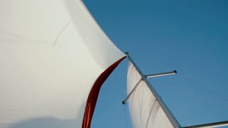 Close-up view of white and red sail waving in the wind in bright summer day. Speed sailboard.