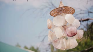 Close-up view of wind chime on a tree. Bright sunny day, decoration for backyard outside.