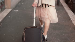 Close-up view of woman s leg walking on the sidewalk carrying the suitcase. Girl arrives and explores the neighborhood.