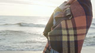 Close-up view of woman standing on the shore of the sea in cold day. Female wrap up in plaid, rug waves in the wind.