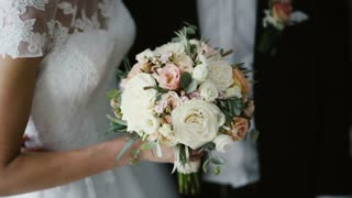 Close-up view of young beautiful bride and room. Man and woman with bouquet standing together after wedding.