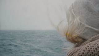 Close-up view of young blonde woman traveling on ship. Attractive female looking on sea and waves, hair waving on wind.