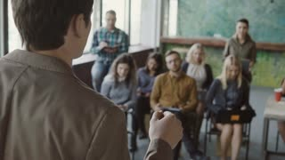 Close-up view of young businessman speaking at seminar at modern office. Mixed race group of people listening the male.