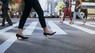 Close-up view of young businesswoman wearing shoes with heels crossing the road in busy downtown. Slow motion.