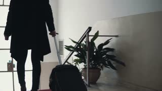 Close-up view of young businesswoman with suitcase. Traveler girl comes downstairs on ladder with baggage.