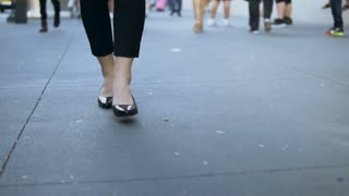 Close-up view of young female walking through the downtown. Businesswoman wearing black shoes with heels. Slow motion.