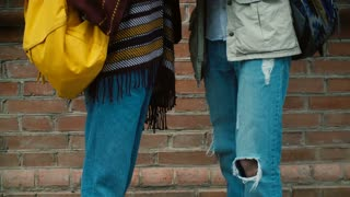 Close-up view of young man and woman legs wearing jeans. Hipster couple with backpack, friends standing and talking.