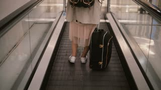 Close-up view of young stylish woman with suitcase standing on the escalator. Feet of attractive female on the airport.