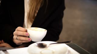 Close-up view of young woman hands holding the white cup. Female sitting in cafe and drinking coffee in the evening.