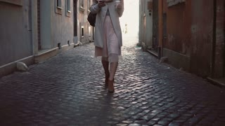 Close-up view of young woman walking at sunny spring city street in Europe. Stylish girl exploring the old town alone.