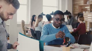 Concentrated African American young man working hard on architecture sketch with colleagues in trendy office space 4K.