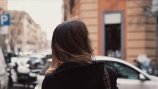 Confused girl looks around in the downtown. Tourist woman with backpack try find way, exploring new city. Slow motion.
