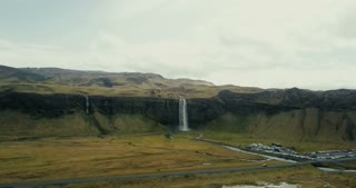 Copter approaches to the powerful waterfall Seljalandsfoss in Iceland. Famous touristic place with amazing view.