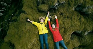Copter flies up from close-up to long shot. Twp happy tourists woman resting on the lava field in Iceland. Happy females