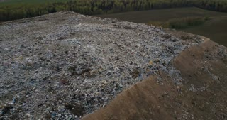 Copter flying around the urban dump with waste trash of life and production. Aerial view of big pile of trash.