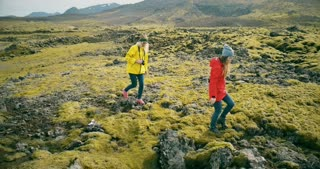 Copter flying around two woman on lava field in Iceland. Tourists with camera walking on the nature and taking photos.