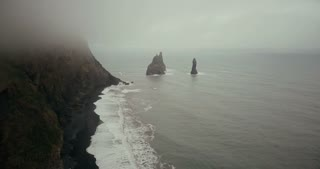 Copter flying over the beautiful black volcanic beach and troll toes cliffs in Iceland. Landscape of sea, fog and waves.