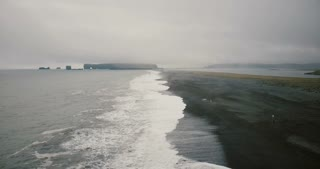Copter flying over the black volcanic beach in Iceland. Beautiful landscape of the water, mountain, waves and fog.