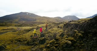 Copter flying over the group of tourists hiking on the mountain. Friend walking in the lava fields in Iceland.