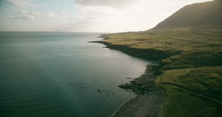 Copter flying over the mountain valley near the water in Iceland. Aerial view of the shore of the sea and meadow.