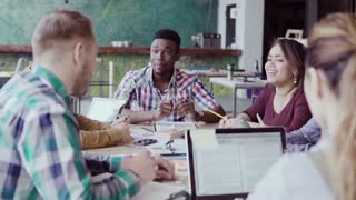 Creative business team meeting in modern office. Mixed race group of young people discussing start-up ideas, laughing.