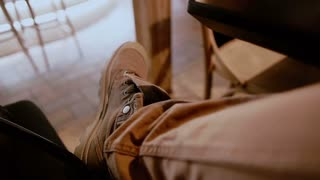 Crossed male legs with brown jeans and boots on under the table in a bar