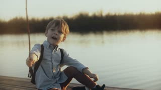 Cute boy child sits with a stick near sunset lake. Portrait of Caucasian child playing angry wild pirate on a pier. 4K.