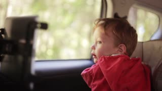 Cute boy sitting in the baby car chair near the window and waiting for something.