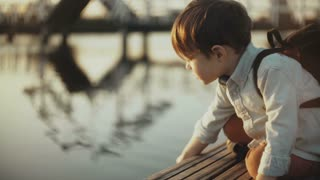 Cute European boy plays with lake water on a pier. Little male child with backpack exploring summer nature. 4K close-up.