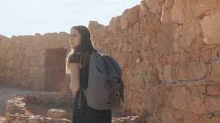 Cute girl with backpack walks along ancient ruins. Pretty European female tourist explores Israel Masada fortress. 4K.