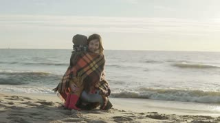 Cute little boy and his mother on shore of sea. Woman with plaid hugs her son and holds on hand. Happy family on beach.