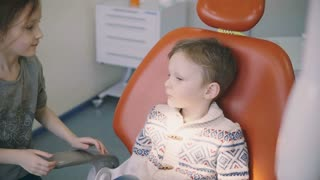 Cute little boy before the doctor reception. Girl kisses brother, sister supports him. Male sitting in dentist chair.