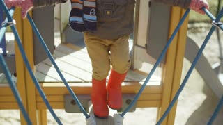 Cute little boy in orange rubber boots walking on playground. Kid carefully makes the first steps at children ropeway.