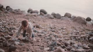 Cute little boy walking near the water through the stones. Male falls on the rocks and rises.