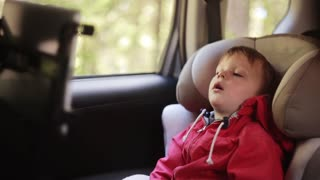 Cute little boy with open-mouthed sitting in the car chair near the window. Tired child in the car.