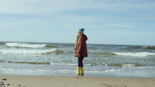 Cute little girl in bright yellow rubber boot at shore of beach. Child looking at the waves from sea, run away from them