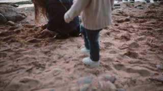 Cute little girl sitting on shore and playing takes sand in hand and then pours on the ground. Brother going to sister.